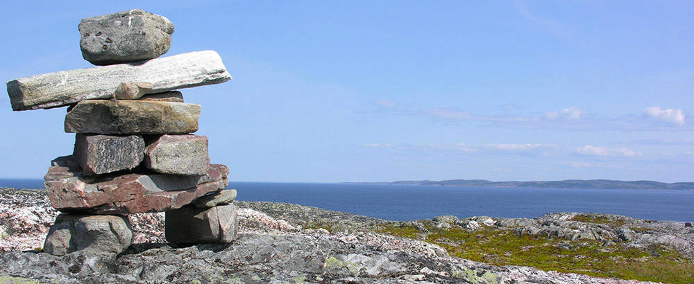 inukshuk-on-hill-overlooking-water-1000x410